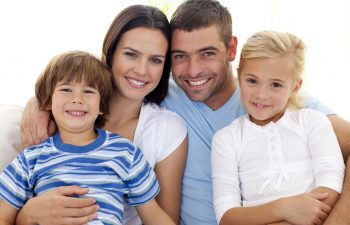 Smiling family with two kids sitting on the couch