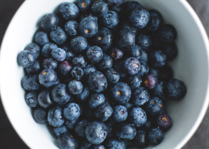 Aerial view of a white bowl filled with blueberries, a food that sometimes causes tooth discoloration