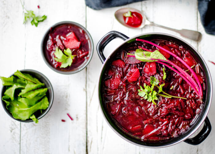 Aerial view of a beet stew on a white wooden counter, a food that causes tooth discoloration