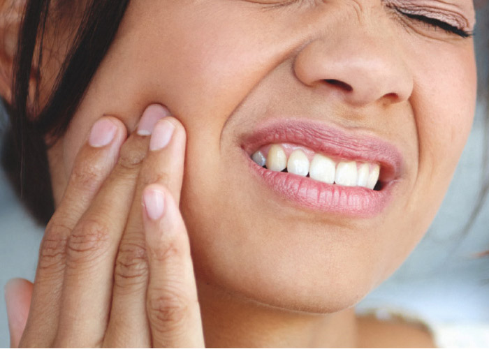 woman holding her jaw wincing with tooth pain