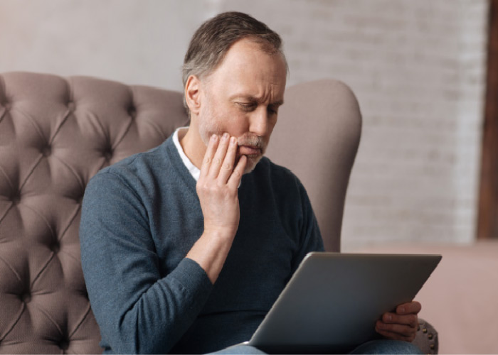 man holding his jaw in pain looking at a computer to learn about gum disease
