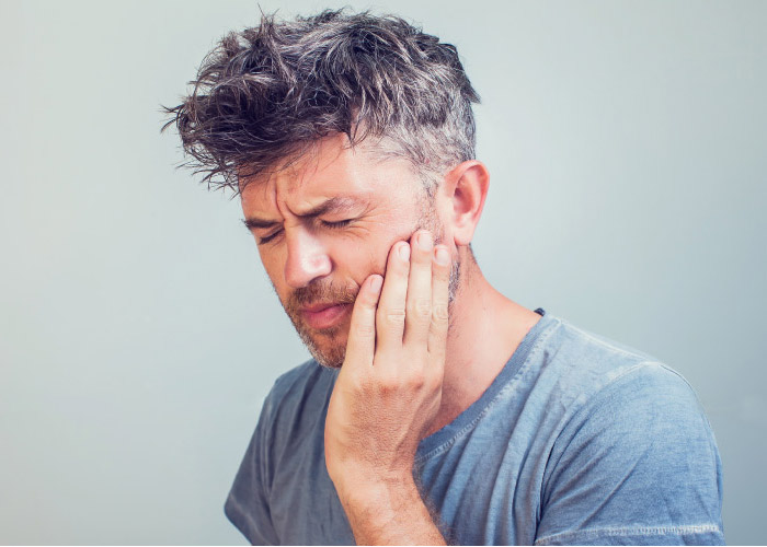 man holding his jaw in pain