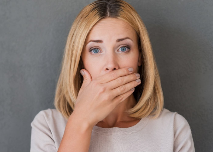 woman covering her mouth with her hand to hide gum disease