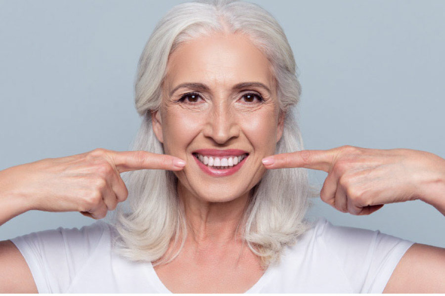 woman pointing to her white teeth with both forefingers after getting professional teeth whitening treatments