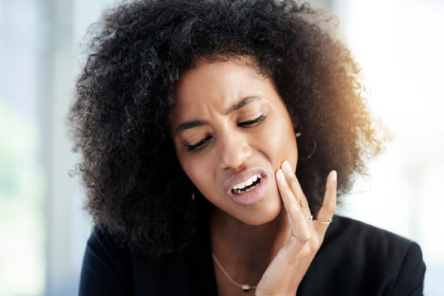 dark haired woman holds her jaw in pain from TMJ