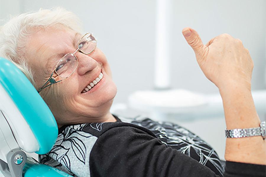 senior woman gives a thumbs up after a good dental checkup