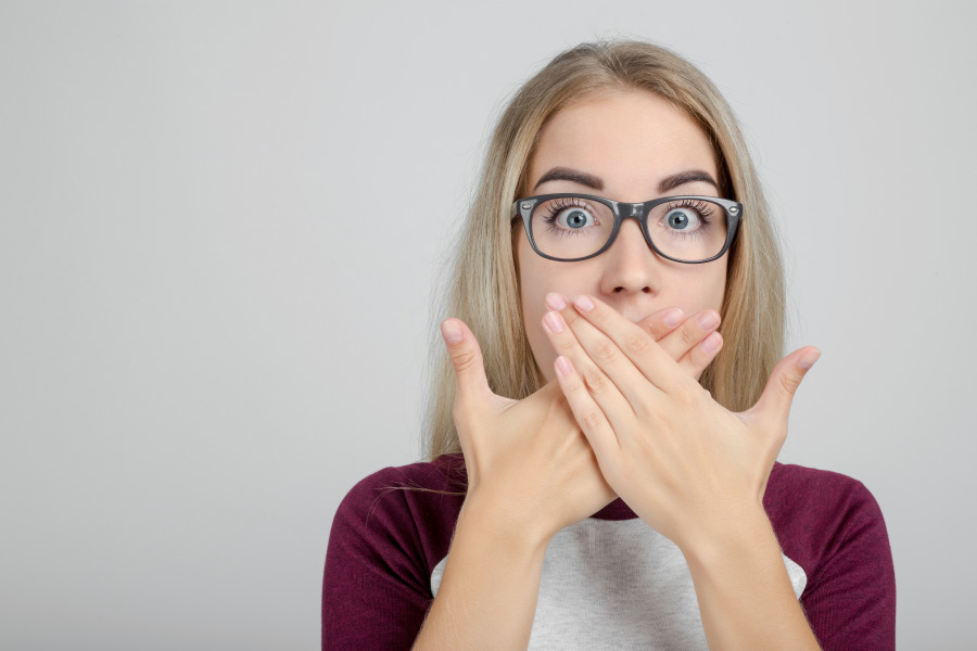 young woman wearing glasses covers her mouth with both hand to hide periodontal pockets