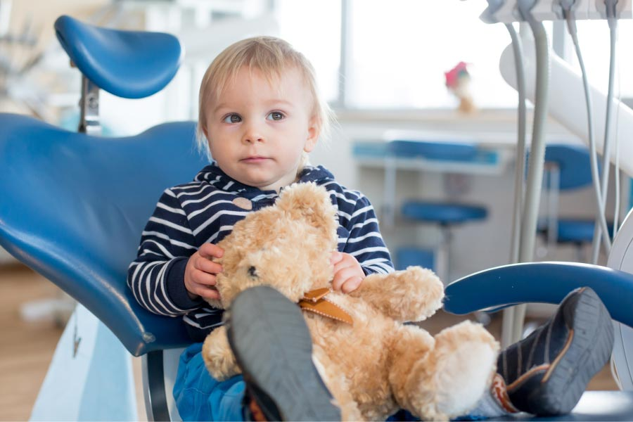 young boy holding a teddy bear sits in the dentist chair