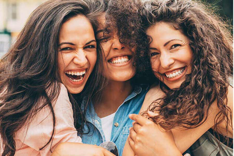 three young women hug and flash their smiles